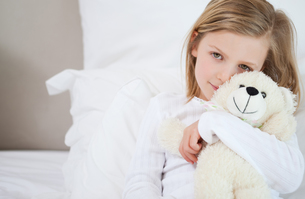 Girl with her teddy sitting on the bedの写真素材 [FYI00484911]