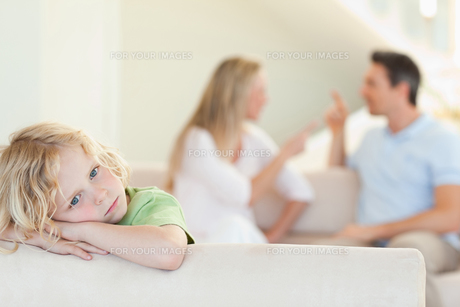 Sad boy with arguing parents behind himの写真素材 [FYI00484913]