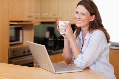 Woman with cup and notebook in the kitchenの写真素材 [FYI00484917]