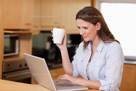 Woman drinking tea while on laptopの写真素材 [FYI00484919]