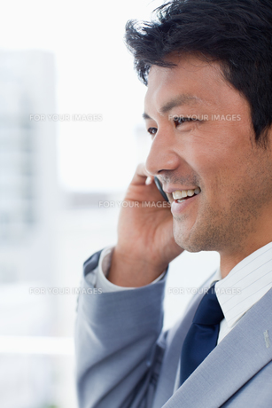 Portrait of a smiling office worker on the phoneの写真素材 [FYI00484925]