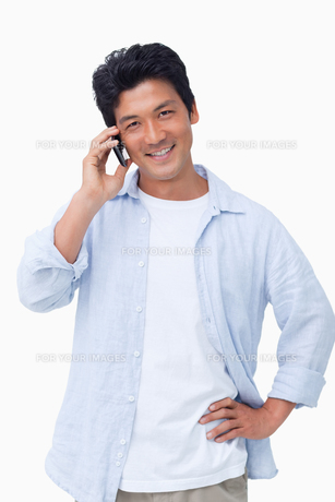 Smiling male on mobile phoneの素材 [FYI00484926]