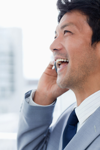 Portrait of a laughing office worker on the phoneの写真素材 [FYI00484930]