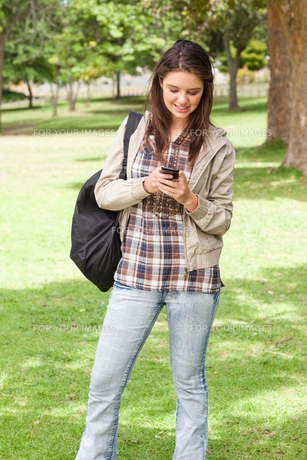 Young student standing while using a smartphoneの写真素材 [FYI00484934]