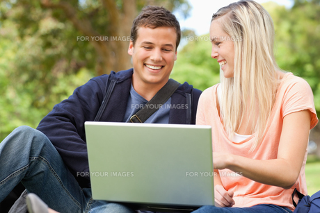 Laughing young people sitting while using a laptopの写真素材 [FYI00484945]
