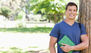 Portrait of a smiling muscled student holding a textbookの写真素材 [FYI00484951]