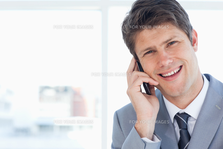 Young businessman laughing while talking on the phoneの写真素材 [FYI00484952]