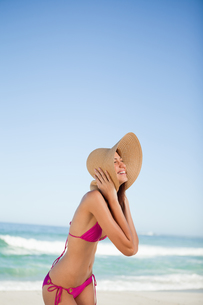 Young woman laughing while standing on the beach and holding her hatの写真素材 [FYI00484954]