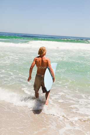 Young blonde man holding his surfboard while walking in the waterの写真素材 [FYI00484961]