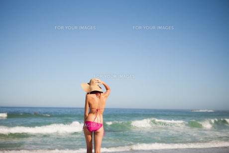 Back view of a young woman in beachwear standing in front of the seaの写真素材 [FYI00484962]