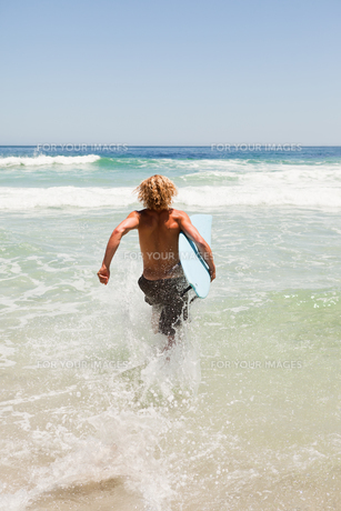 Young blonde man holding his blue surfboard while running in the waterの写真素材 [FYI00484964]