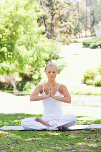 Woman in a yoga position sitting on the lawnの写真素材 [FYI00484966]