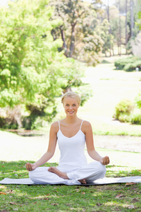 Smiling woman sitting in a yoga position in the parkの写真素材 [FYI00484968]