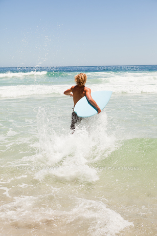 Blonde man running fast in the water while holding his surfboardの写真素材 [FYI00484969]