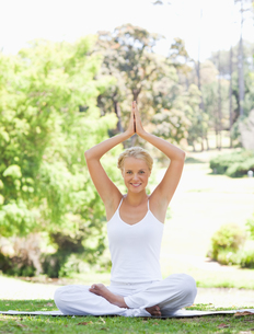 Smiling woman sitting in a yoga position on the grassの写真素材 [FYI00484971]