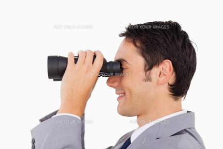 Close up of a businessman using binocularsの写真素材 [FYI00484989]