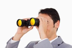 Man in a suit using binocularsの写真素材 [FYI00484993]
