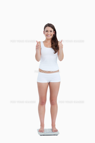 Smiling woman with her thumbs up while standing on weighing scalesの写真素材 [FYI00484997]