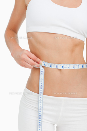 Close up of a slim woman measuring her waistの写真素材 [FYI00485011]