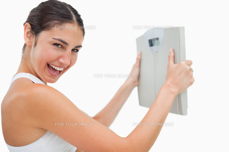 Cheerful young woman holding a scalesの写真素材 [FYI00485014]
