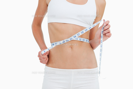 Close up of a woman on diet measuring her waistの写真素材 [FYI00485016]