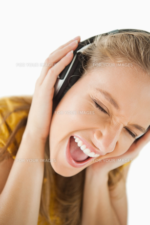 Close up of a blonde woman enjoying music with headphonesの写真素材 [FYI00485017]
