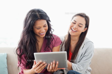 A laughing pair of women on the couch watching their tablet pcの素材 [FYI00485049]
