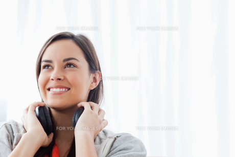 A woman looking slightly upwards and smiling with headphonesの写真素材 [FYI00485050]