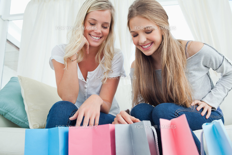 Girls looking into their shopping bags for a item to try onの写真素材 [FYI00485054]