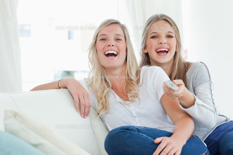 Laughing sisters sitting on the couchの写真素材 [FYI00485056]