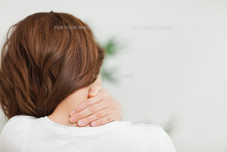 Close up of a brunette woman massing her neckの素材 [FYI00485067]