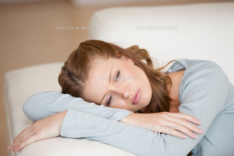 Woman lying on a sofa crossing her arms looking downの素材 [FYI00485068]