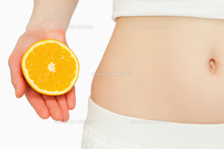 Woman placing an orange near her bellyの写真素材 [FYI00485069]