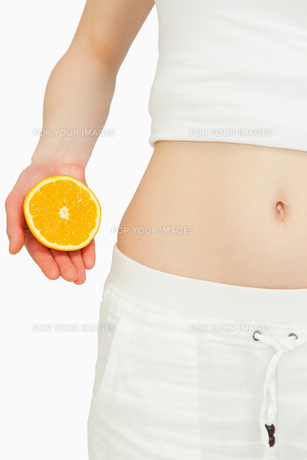 Close up of a woman placing an orange near her bellyの写真素材 [FYI00485074]