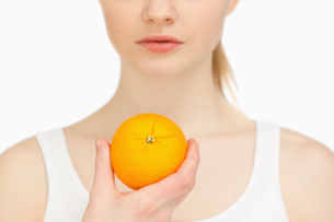 Woman holding an orangeの写真素材 [FYI00485078]