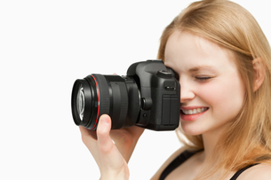 Smiling woman holding a cameraの写真素材 [FYI00485080]