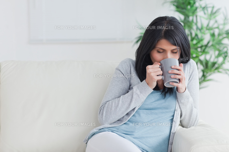 Woman drinking a mug while relaxing on a sofaの写真素材 [FYI00485083]