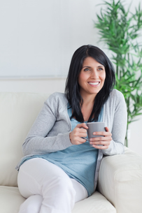 Woman sitting on a couch while holding a grey mugの写真素材 [FYI00485092]