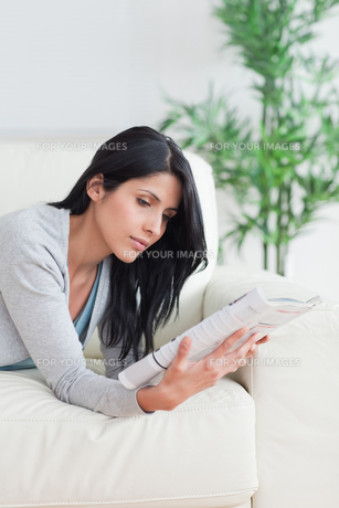 Woman reading a magazine while relaxing on a couchの写真素材 [FYI00485093]