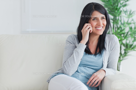 Woman talking on the phone while relaxing on a couchの写真素材 [FYI00485094]