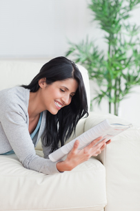Woman smiling while she reads a magazineの写真素材 [FYI00485100]