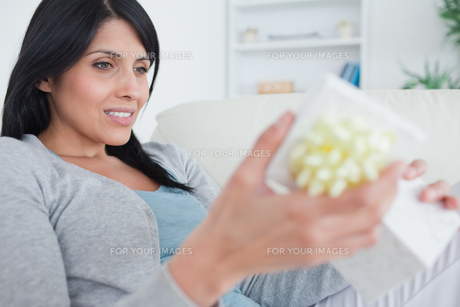 Woman sitting on a couch while opening a gift boxの写真素材 [FYI00485108]