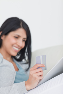 Woman looking at a tactile tablet while holding a credit cardの写真素材 [FYI00485112]
