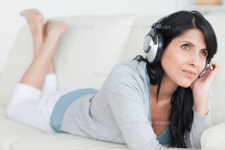 Woman lying on a couch with headphones onの写真素材 [FYI00485113]
