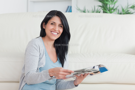 Smiling woman holding a magazine while leaning on a couchの写真素材 [FYI00485117]