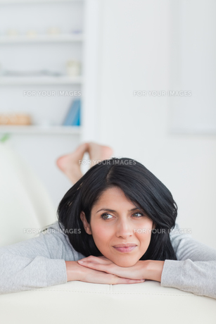 Woman relaxing on a couch holding her head with two handsの写真素材 [FYI00485121]