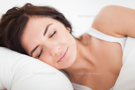 Peaceful brown-haired woman sleeping in the bedの素材 [FYI00485127]