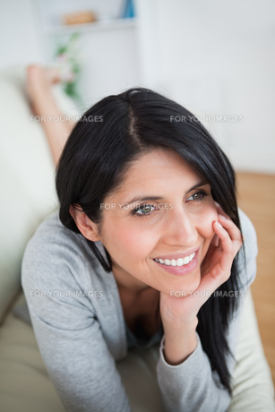 Woman smiling as she holds her head with her fist on a couchの写真素材 [FYI00485131]