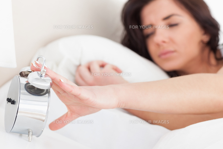 Brunette woman trying to turn off her alarm clockの素材 [FYI00485136]
