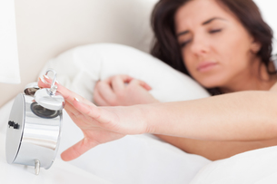 Brunette woman trying to turn off her alarm clockの写真素材 [FYI00485136]